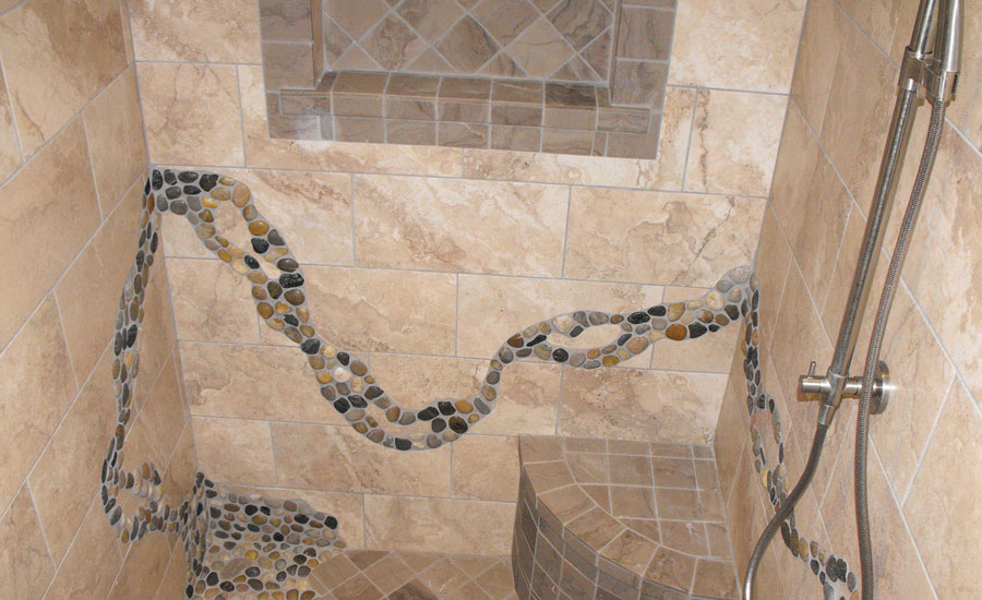 Curving stone tile insets blend with curves in shower and tub installation