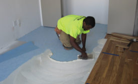 An installer from ReSource New Jersey installs engineered hardwood flooring